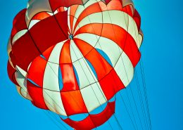 white and red parachute in the blue sky wth bright sun behind