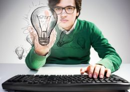 Idea concept with concentrated young man sitting at desk with keyboard and pointing at abstract lightbulb sketch